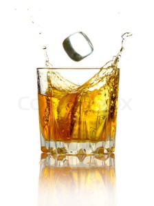 Splash in glass of whiskey and ice isolated