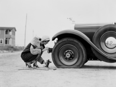 h-armstrong-roberts-woman-changing-flat-tire-on-car